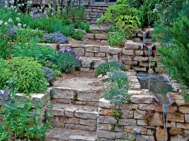 Ein Beispiel für einen Hanggarten: Trocken aufgesetzte Kalksteinmauern und trogförmigen Bachlaufschalen, die Stufenbepflanzung passt zum rustikalen Flair.