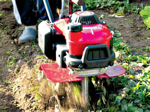 Beete vorbereiten, indem der Boden mit einer Maschinegelockert wird.