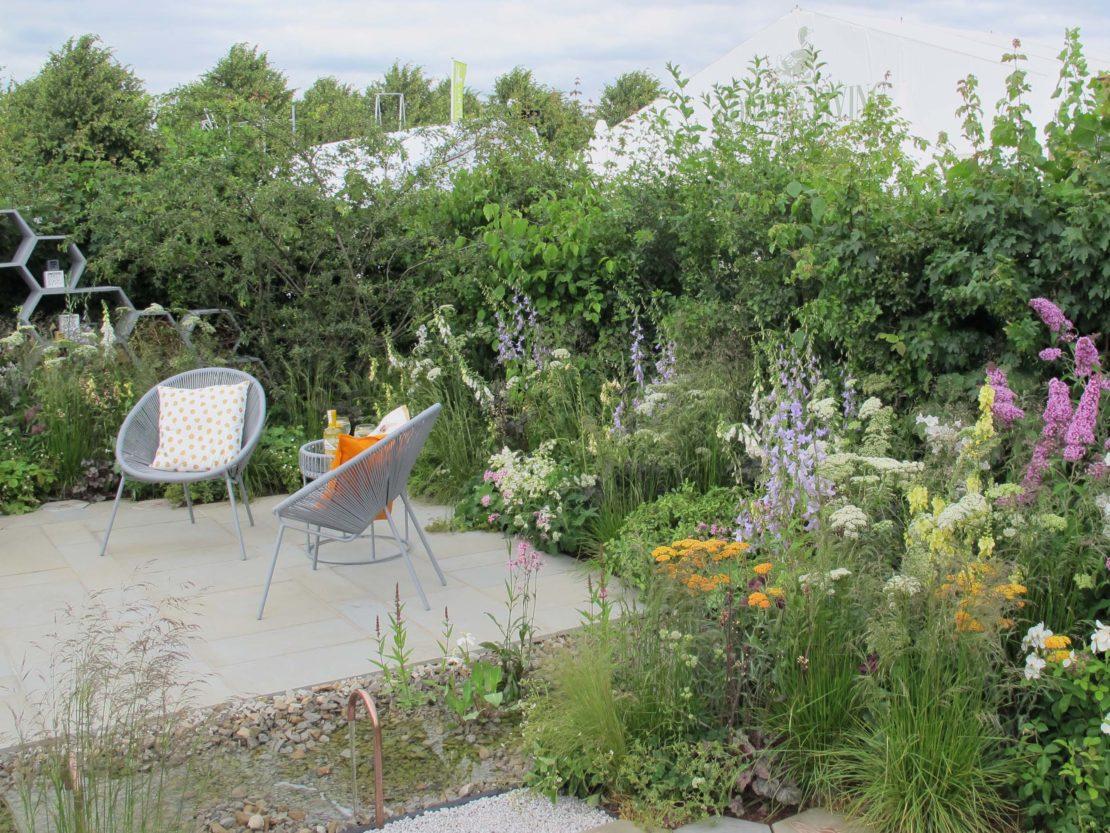 Ein befestigter Sitzplatz im Garten, von bienenfreundlichen Pflanzen umgeben und mit einem flachen, mit Kieseln ausgelegten Wasserlauf.