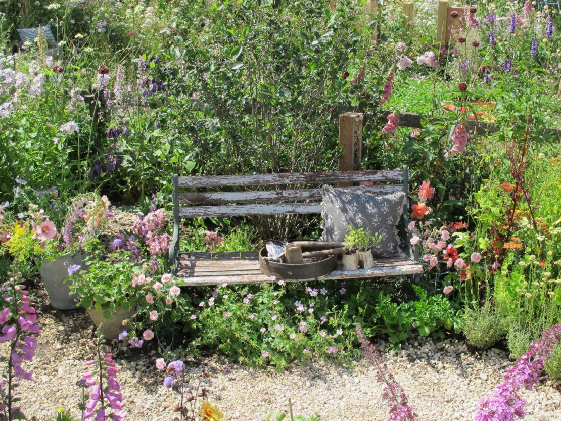Eine Gartenbank, von blühenden Pflanzen umgeben, dahinter der Nachbargarten, der weder durch eine Mauer oder Hecke abgetrennt ist - solche lockeren Grenzen machen es Igeln leicht, von einem Garten zum anderen zu gelangen.