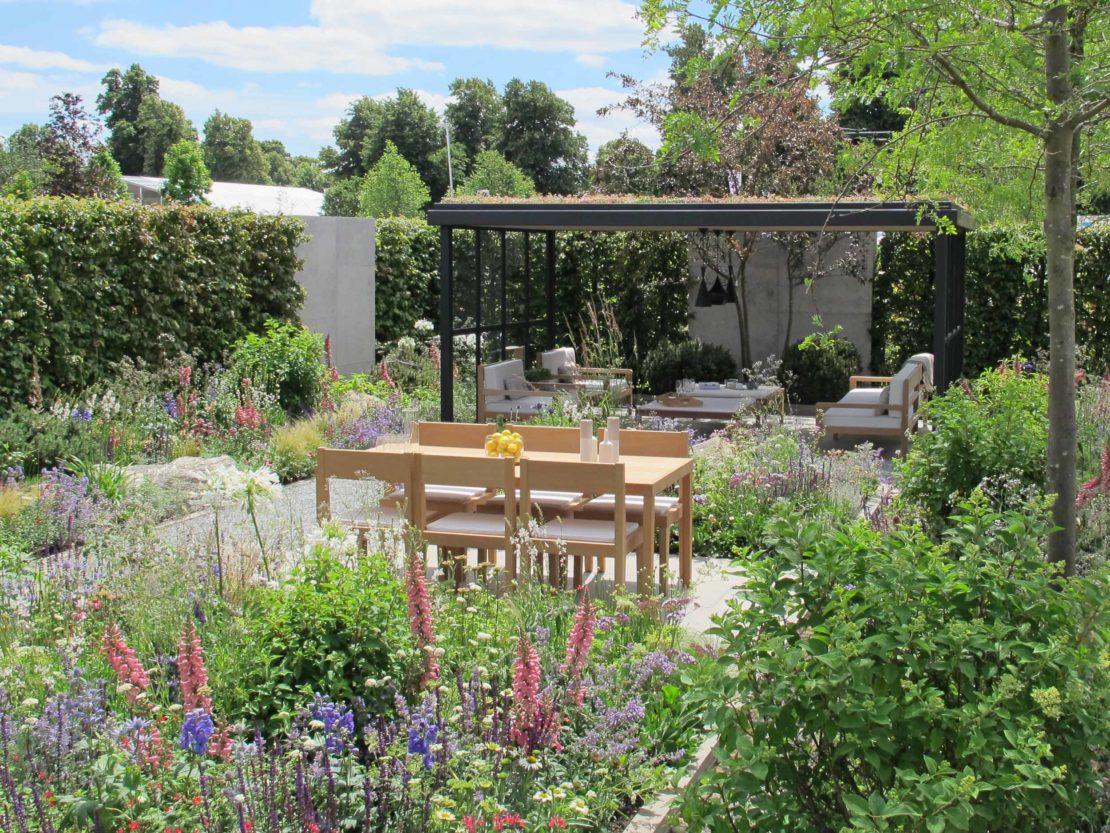 Viele blühende Stauden und ein schlichter Gartenpavillon lassenn den Lagom-Garten sehr natürlich wirken.