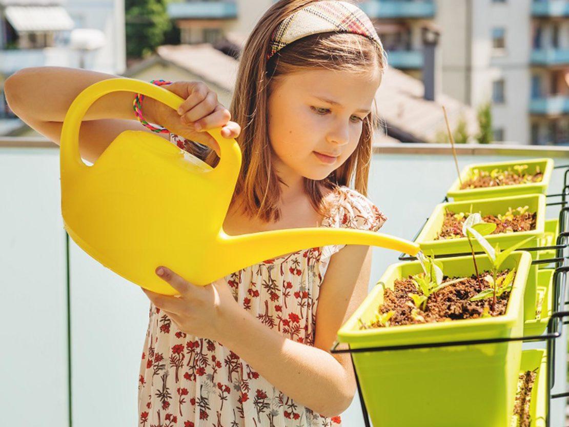 Mädchen gießt Jungpflanzen in Balkonkasten