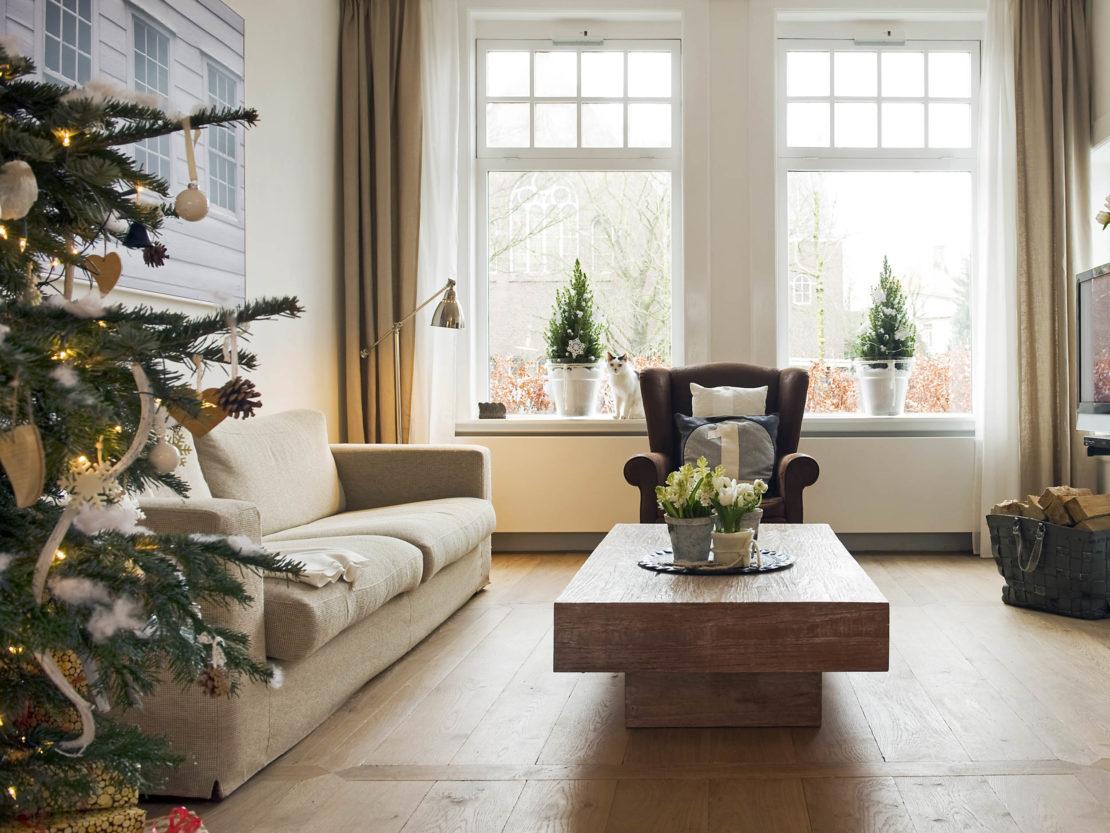 ein Wohnzimmer mit zwei Weihnachtsbäumchen auf der Fensterbank und einem geschmückten Weihnachtsbaum