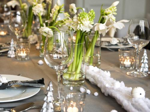 festliche Tischdeko mit weißblühenden Zwiebelblumen und kleinen weißen Weihnachtsbäumen