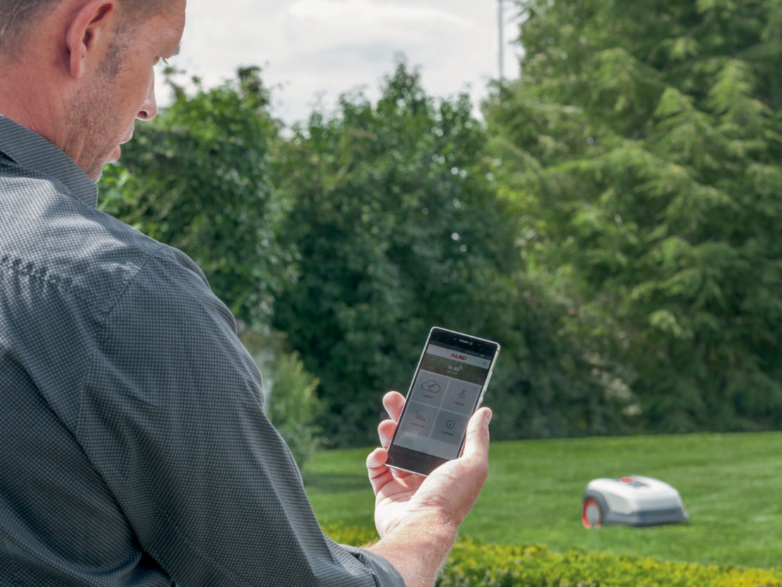 Ein Mann steuert einen Mähroboter vom Smartphone aus.