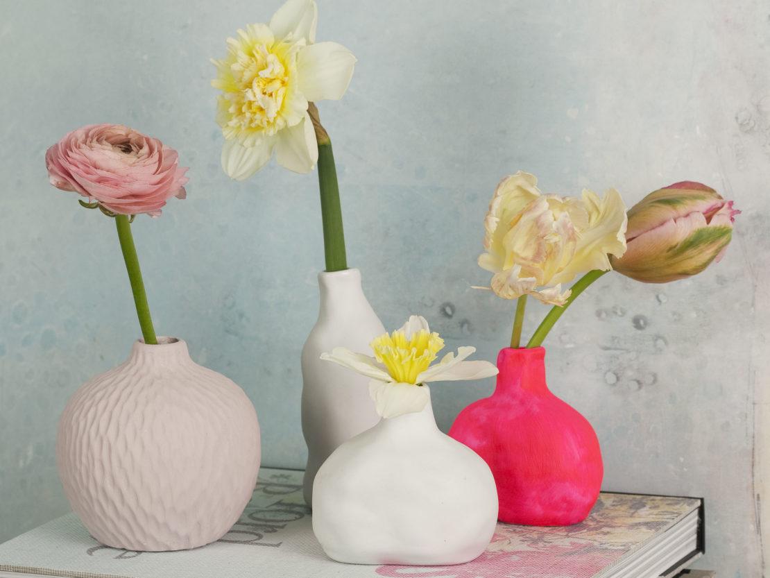 blühende Frühlingsblumen einzeln in kleinen Vasen arrangiert