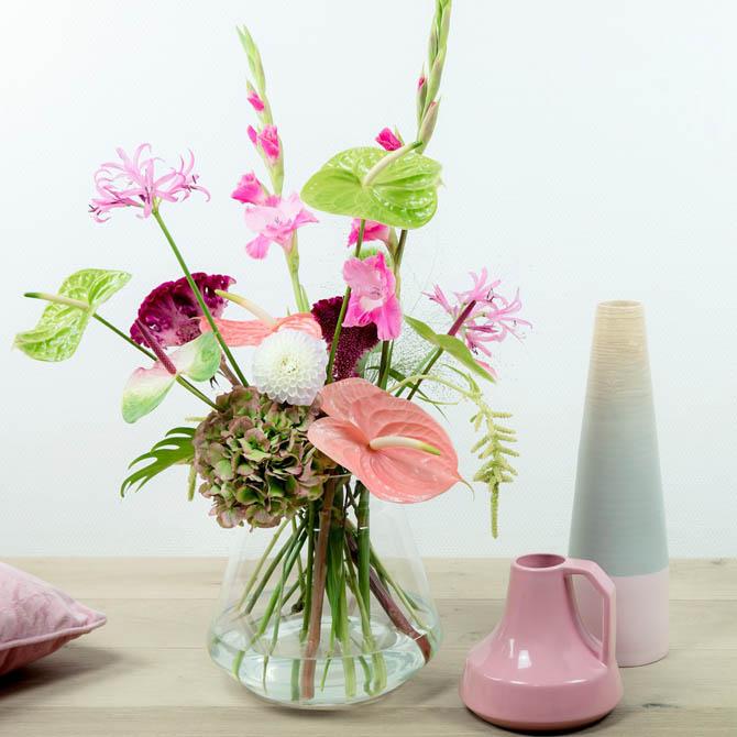 Schnittblumenarrangement mit Flamingoblumen in einer Glasvase